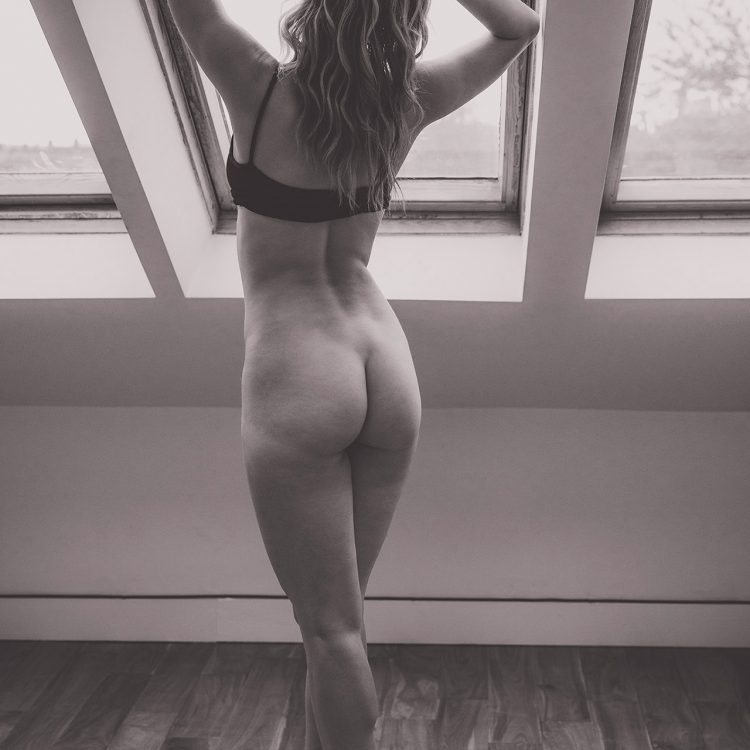 Nude model poses by apartment window in Belfast
